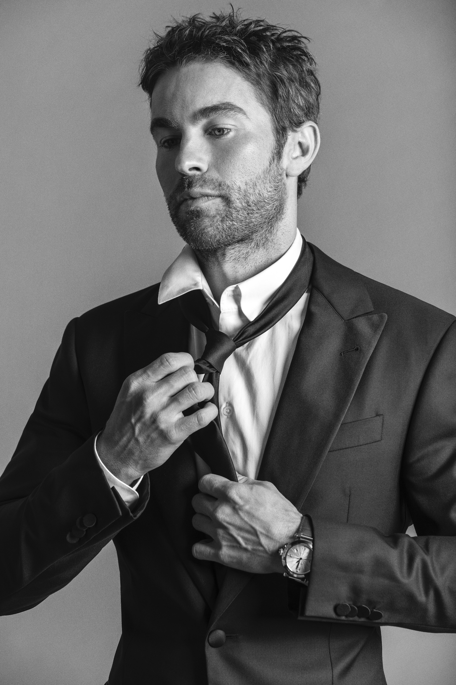 Chace wears a suit jacket, pants, shirt, and tie Giorgio Armani and watch Pasha de Cartier.